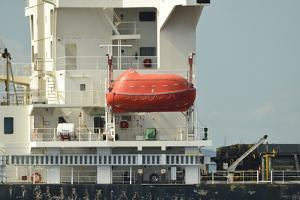 A Orange Life Raft Hangs at the Ready from the Side of a Commercial Freighter at Anchor by Jonathan Kingston