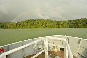 A Rainbow over the Bow of a Small Passenger Ship at Anchor Off of Barro Colorado Island by Jonathan Kingston