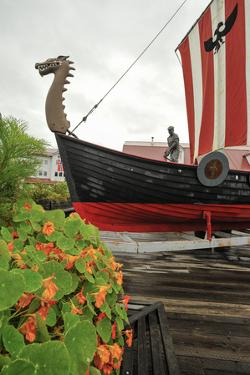 A Red and Black Viking Ship and a Statue of a Fisherman in Petersburg, Alaska by Jonathan Kingston
