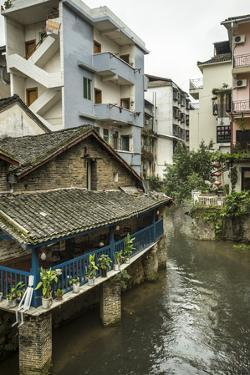 A Restaurant and Apartments Rise Above a River in Yangshuo, China by Jonathan Kingston