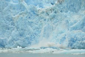 A Serac Falls Off the Face of the Dawes Glacier into Tracy Arm Fjord by Jonathan Kingston