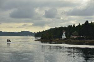 A Small Boat Passes a Lighthouse on a Forested Coast by Jonathan Kingston