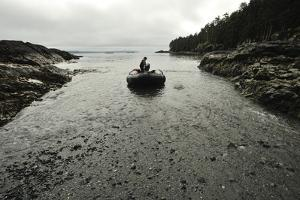 A Small Inflatable Boat Pulls onto the Rocky Shore of Sgang Gwaay by Jonathan Kingston