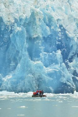 A Small Inflatable Boat with Tourists Is Dwarfed by the Massive Face of Dawes Glacier by Jonathan Kingston