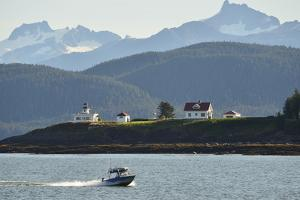 A Small Motorboat Cruises Past the Point Retreat Lighthouse by Jonathan Kingston