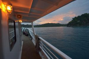 A Small Passenger Ship Pulls into a Bay at Sunrise in Manuel Antonio National Park by Jonathan Kingston
