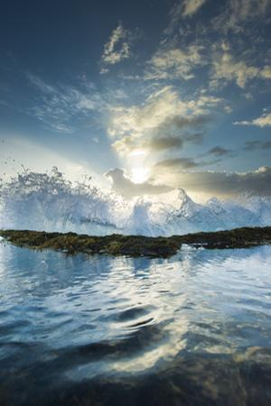 A Wave, Back Lit by the Sunrise, Breaks over the Rocky North Shore of Molokai, Hawaii by Jonathan Kingston