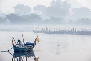 An Indian Man Rowing a Boat Across the Yamuna River in Morning Fog by Jonathan Kingston