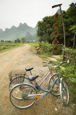 Bicycles Are Parked on a Road by a Restaurant Near Yangshuo, China by Jonathan Kingston