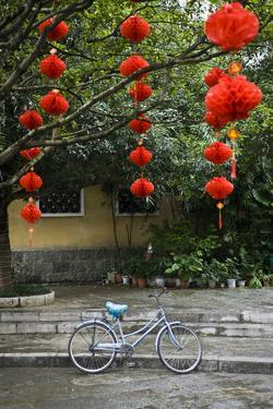 Decorations Hang From Branches Above a Blue Bike in Yangshuo, China by Jonathan Kingston