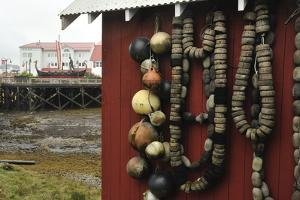 Fishing Floats Hung on the Side of a Red Building. a Viking Ship in the Background by Jonathan Kingston