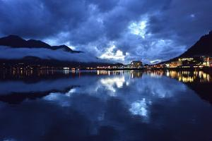 Juneau's Lights Reflect in the Calm Waters of Gastineau Channel as Storm Clouds Clear by Jonathan Kingston