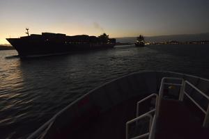 Large Container Ships Pass Each Other at Sunset in the Entrance to the Panama Cana by Jonathan Kingston