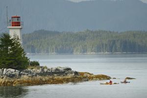 Sea Kayakers Paddle Past a Lighthouse on a Rocky Coast by Jonathan Kingston