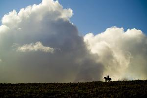 Silhouette of a Cowboy Riding across a Ridge with a Cumulonimbus Cloud in the Background by Jonathan Kingston