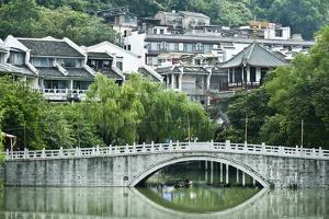 Stone Arch Bridge in Front of a Small Village Near Yangshuo, China by Jonathan Kingston