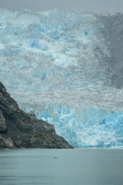 The Blue Face of Dawes Glacier Rises Above the Waters of Tracy Arm Fjord on a Rainy Day by Jonathan Kingston
