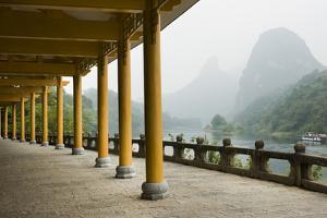 The Li River Runs Past a Covered Walkway by the Karst Formations by Jonathan Kingston