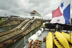 The Panamanian Flag Flies over the Upper Deck of a Passenger Ship as it Transits Locks by Jonathan Kingston