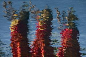 The Reflection of Hula Dancers, Dressed in Red, Dancing on the Edge of a Pool in Molokai, Hawaii by Jonathan Kingston