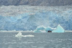 Tourists in an Inflatable Boat Inspect a Large Iceberg in the Water at Dawes Glacier by Jonathan Kingston