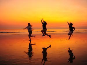 Silhouetted Children Playing on the Beach at Sunset by Jorge Fajl