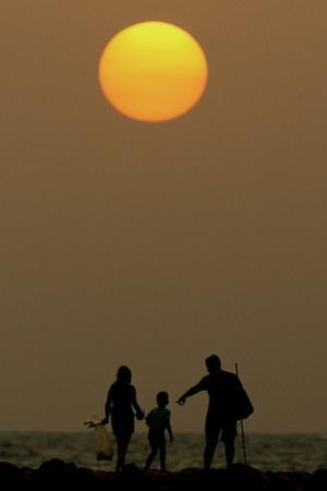 Colombian Family Walks at Sunset on Bocagrande Beach in the Caribbean Port of Cartagena