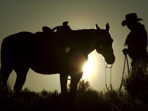 Cowboy With His Horse at Sunset, Ponderosa Ranch, Oregon, USA by Josh Anon