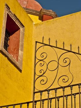 Wrought Iron Fence Against a Yellow Church Wall with Barred Window Against a Blue Sky, Mexico by Judith Zimmerman