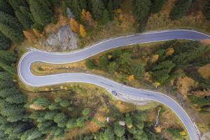 A view by drone of a winding road in the Dolomites, Italy by Julian Elliott