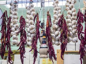 Italy, Florence. Garlic and peppers for sale hanging in a shop in the Central Market by Julie Eggers