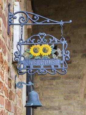 Italy, Tuscany. A wrought iron welcome sign in the village of Chiusure in the province of Siena. by Julie Eggers