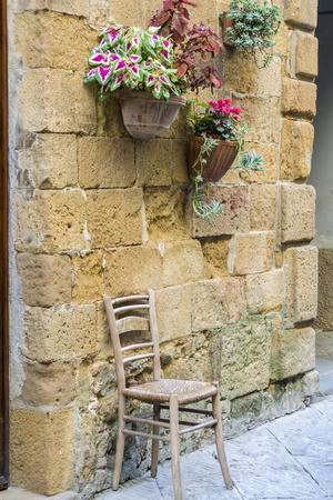 Italy, Tuscany. Chair and flower pots outside the entrance to a shop in a village in Tuscany.