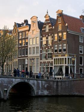 Netherlands, Amsterdam. Traditional houses along the canals and bridge crossing. by Julie Eggers