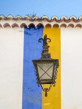 Portugal, Obidos. Wrought iron lantern hanging from a colorful stripped wall in the walled town. by Julie Eggers