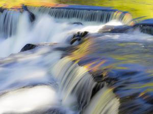 US, Michigan, Upper Peninsula. Water flowing over Bond Falls with reflections. by Julie Eggers