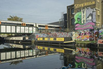 Overground train drives past canal by artists studios and warehouses in Hackney Wick, London, Engla