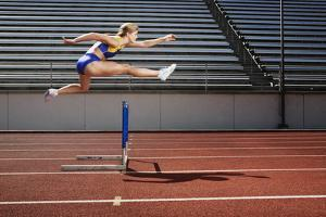Athletic Woman Jumping over Hurdle by Jupiterimages