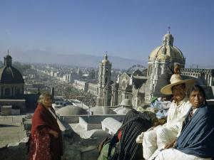 Four People Sit on Rooftop Overlooking Our Lady of Guadalupe Church by Justin Locke