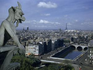 Gargoyle on Notre Dame Looks Down on a Densely Packed Cityscape by Justin Locke