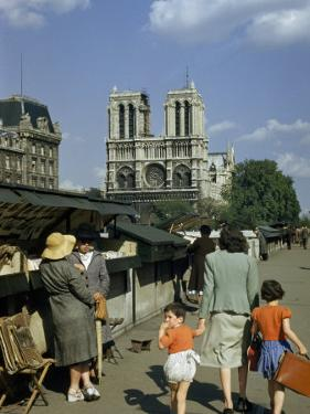 Mother Hurries Children Past Book Stalls Near Notre Dame De Paris by Justin Locke