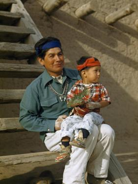 Native American Father and Son Dressed for a Dance Sit Together by Justin Locke