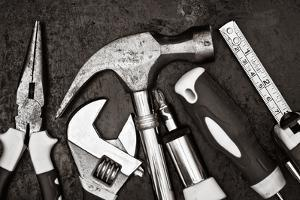 Black and White Image of a Set of Tools on a Textured Metallic Background by Kamira