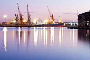 Commercial Docks at Sunset with a Ship and Cranes by Kamira