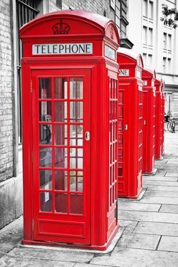 Row Of Iconic London Red Phone Cabins With The Rest Of The Picture In Black And White by Kamira