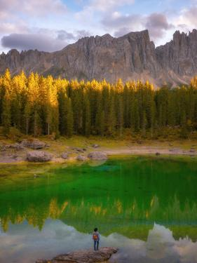 Young man observing the beauty of Lago Di Carezza at sunset, Dolomites, Italy by Karen Deakin
