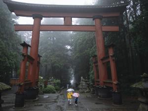 Tourists with Umbrellas Walk under an Arch at the Base of Mount Fuji by Karen Kasmauski