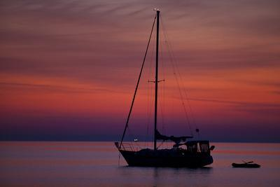 A Lone Sailboat Sits on Quiet Water at Dawn Just before Sunrise Off Tilghman Island, Maryland