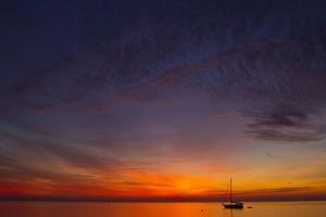 A Lone Sailboat Sits on the Calm Waters of the Chesapeake Bay Off Tilghman Island, Maryland by Karine Aigner