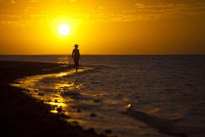 A Silhouette of a Woman Walking in the Waves of the Surf at Sunset in Holbox Island, Mexico by Karine Aigner